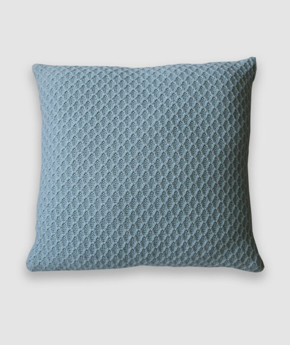 Confeccionada em tricô no ponto colmeia na cor asturias. O preenchimento é feito em fibra siliconada. Possui zíper invisível.