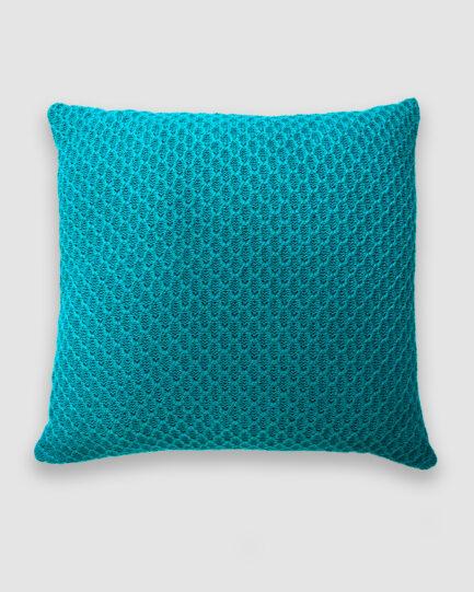 Confeccionada em tricô no ponto colmeia na cor fonte. O preenchimento é feito em fibra siliconada. Possui zíper invisível.