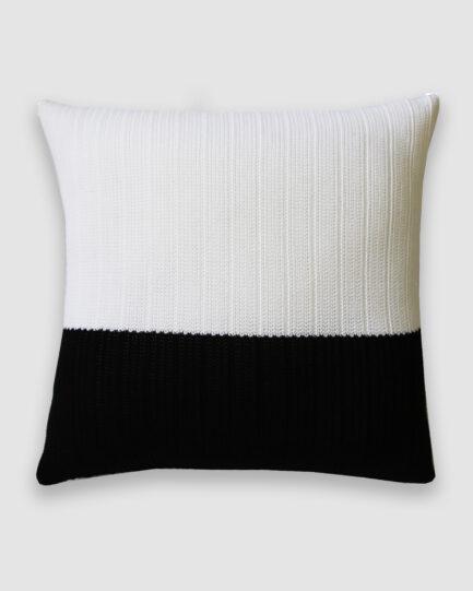 Confeccionada em tricô no ponto links na cor preto e branco. O preenchimento é feito em fibra siliconada. Possui zíper invisível.