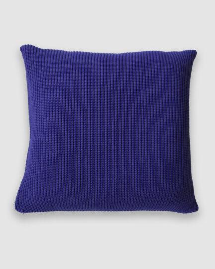 Confeccionada em tricô no ponto pérola na cor azul bic. O preenchimento é feito em fibra siliconada. Possui zíper invisível.