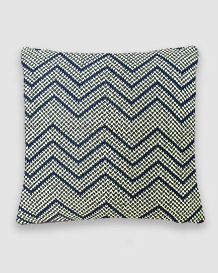 Confeccionada em tricô no ponto zig zag na cor preto e branco. O preenchimento é feito em fibra siliconada. Possui zíper invisível.