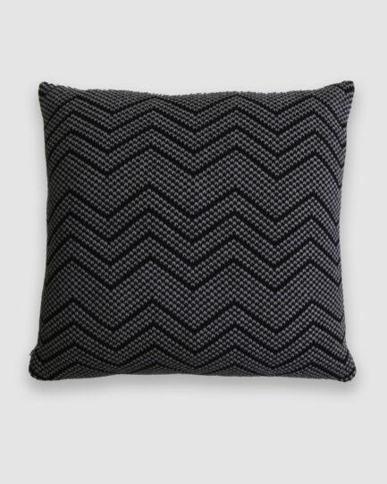 Confeccionada em tricô no ponto pérola na cor preto e new grey. O preenchimento é feito em fibra siliconada. Possui zíper invisível.