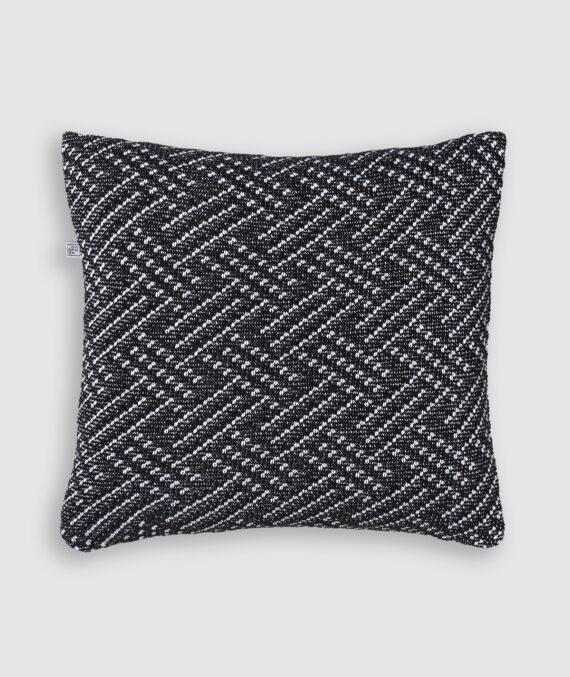 Confeccionada em tricô na cores preto e branco. O preenchimento é feito em fibra siliconada. Possui zíper invisível.