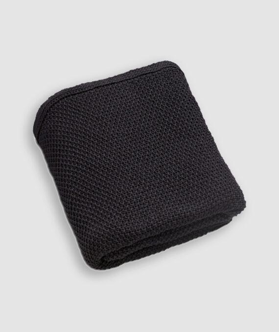 Manta da Coleção De Tempos em Tempos lançada pela Codex Home. Confeccionada em tricot no ponto arroz na cor preta.