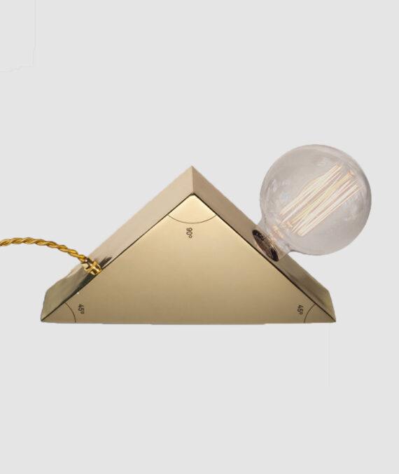 A Luminária Triângulo Isósceles é feita de aço carbono e possui uma gravação a laser nos ângulos.
